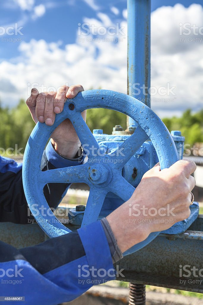 Hands close-up of mature manual worker turning stop-gate valve stock photo