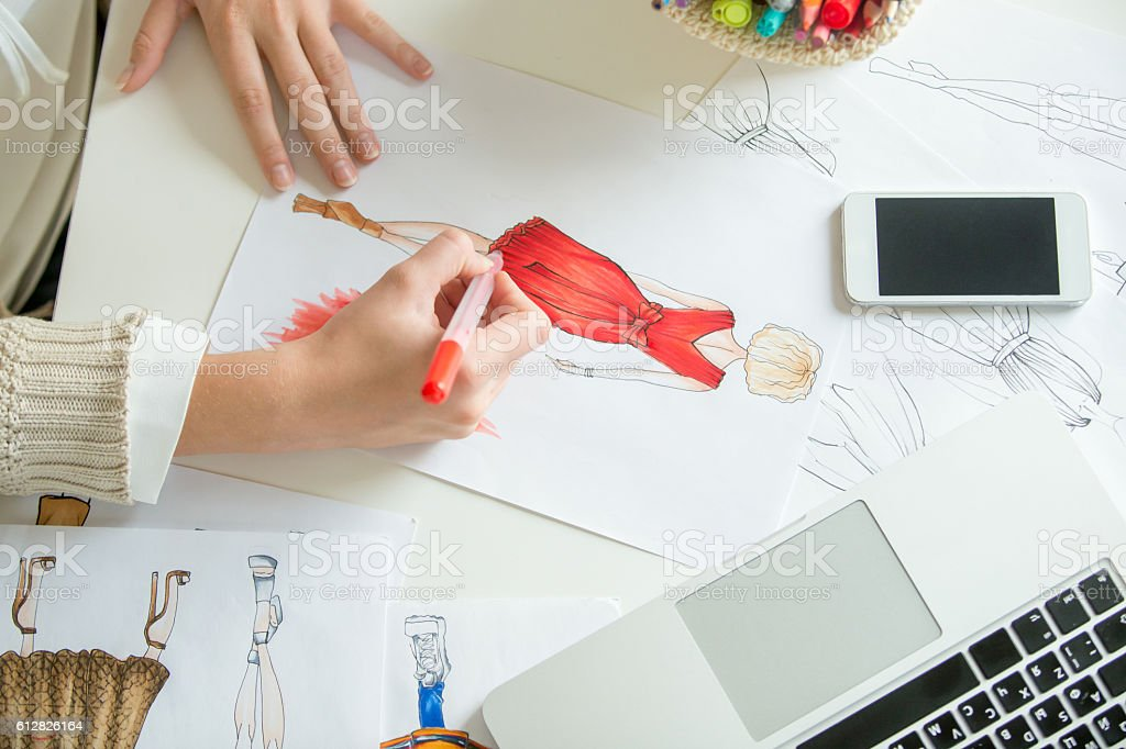 Hands colouring a clothing design sketch stock photo
