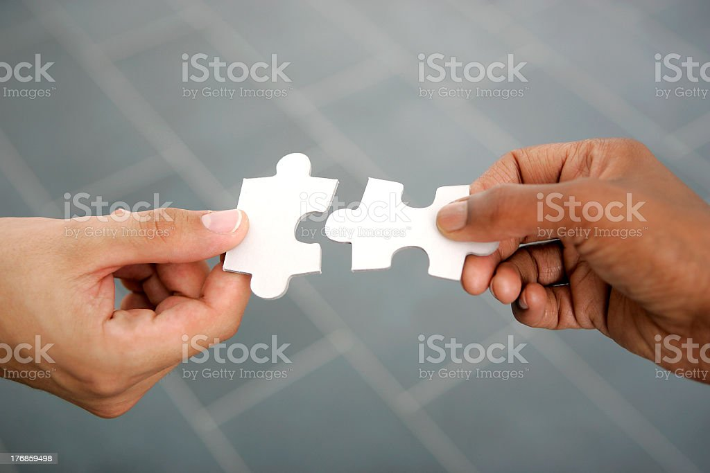 Hands connecting puzzle pieces royalty-free stock photo