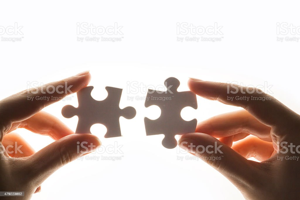 Hands connecting two white puzzle pieces stock photo