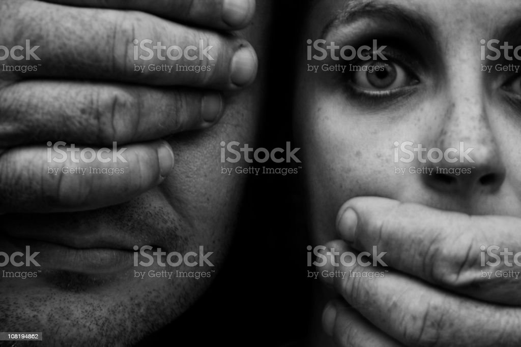 Hands Covering Man's Eye and Startled Woman's Mouth stock photo