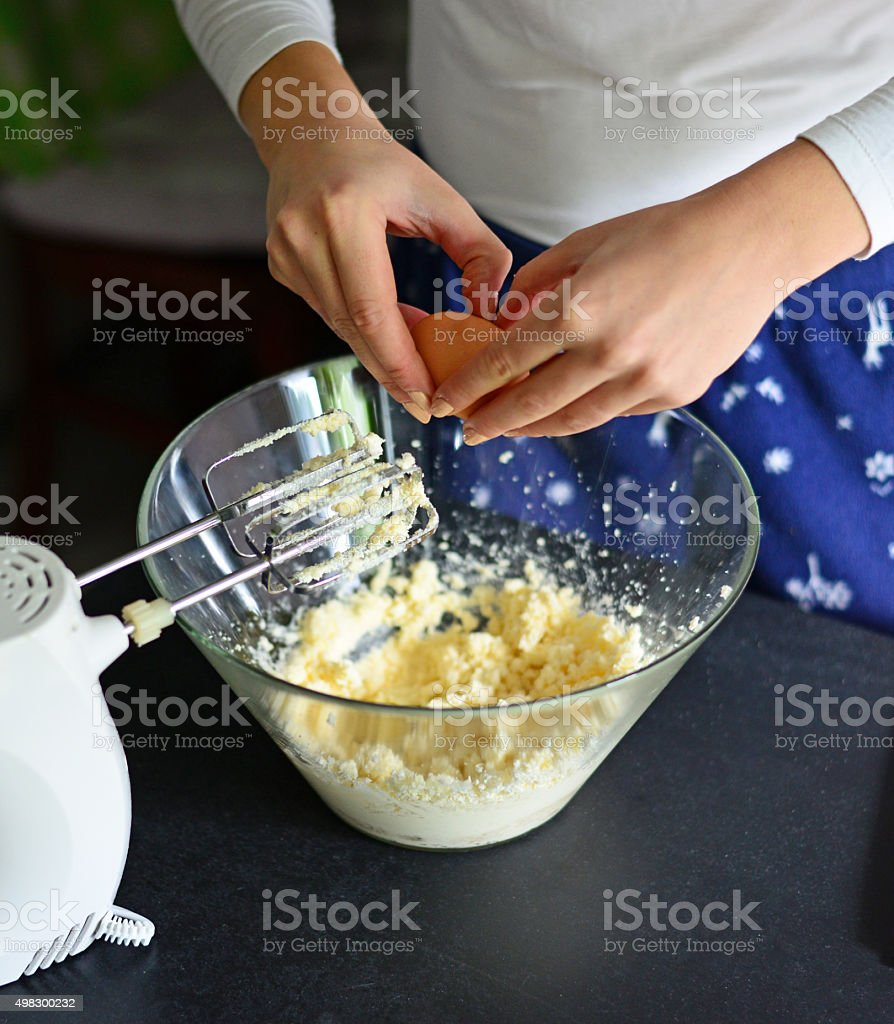 hands cracking an egg into a glass bowl stock photo