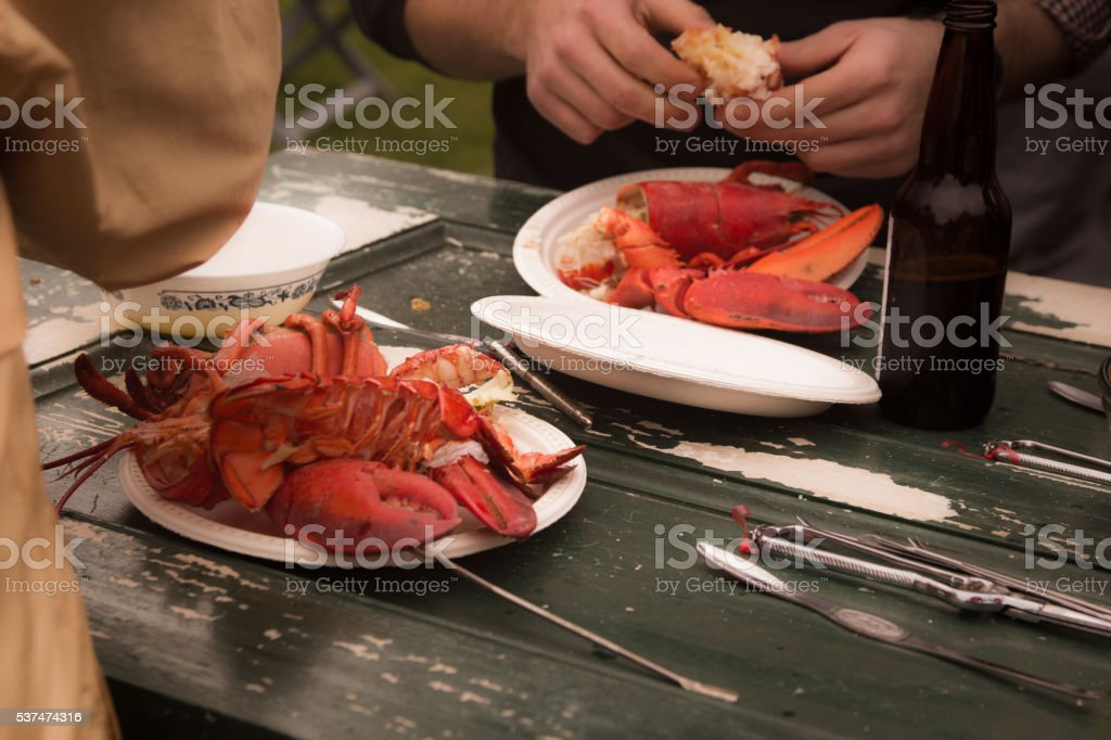 Hands cracking lobsters on a wooden picnic table stock photo