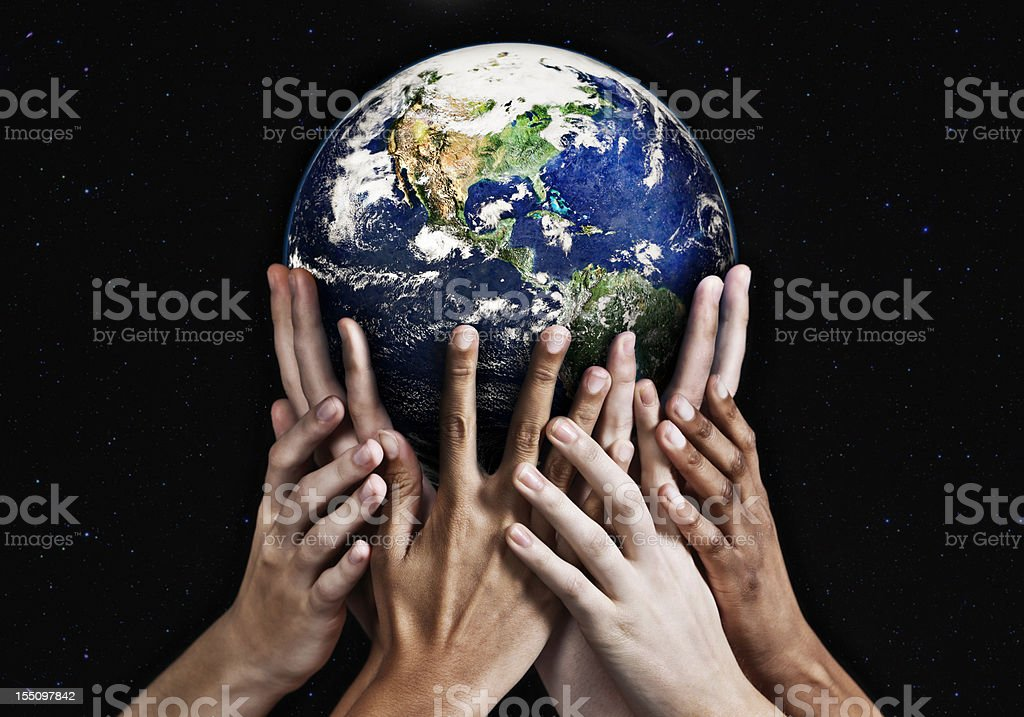 Hands cradling Mother Earth against starfield background stock photo
