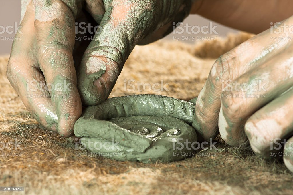 hands creating a craft from blue clay stock photo