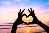 Hands creating shape of heart, symbol of love, friendship, harmony