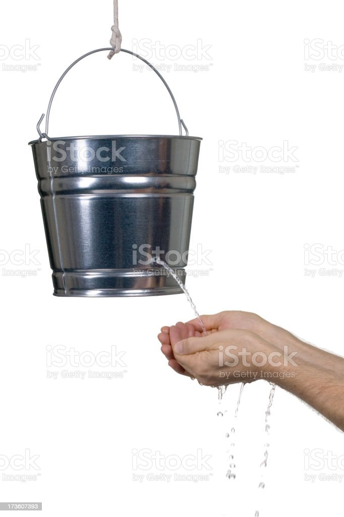 Hands cupped under a silver bucket leaking water stock photo