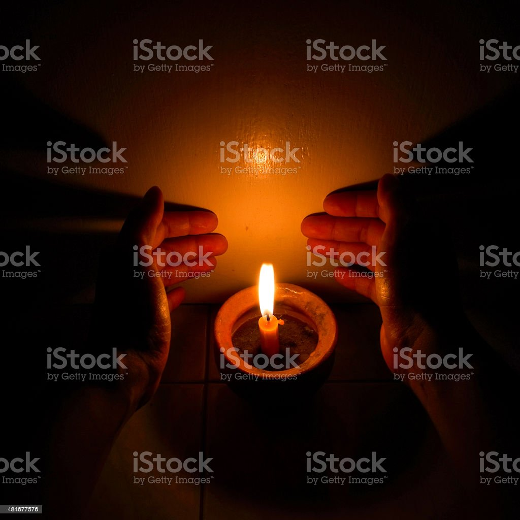 Hands cupping around a burning candle stock photo
