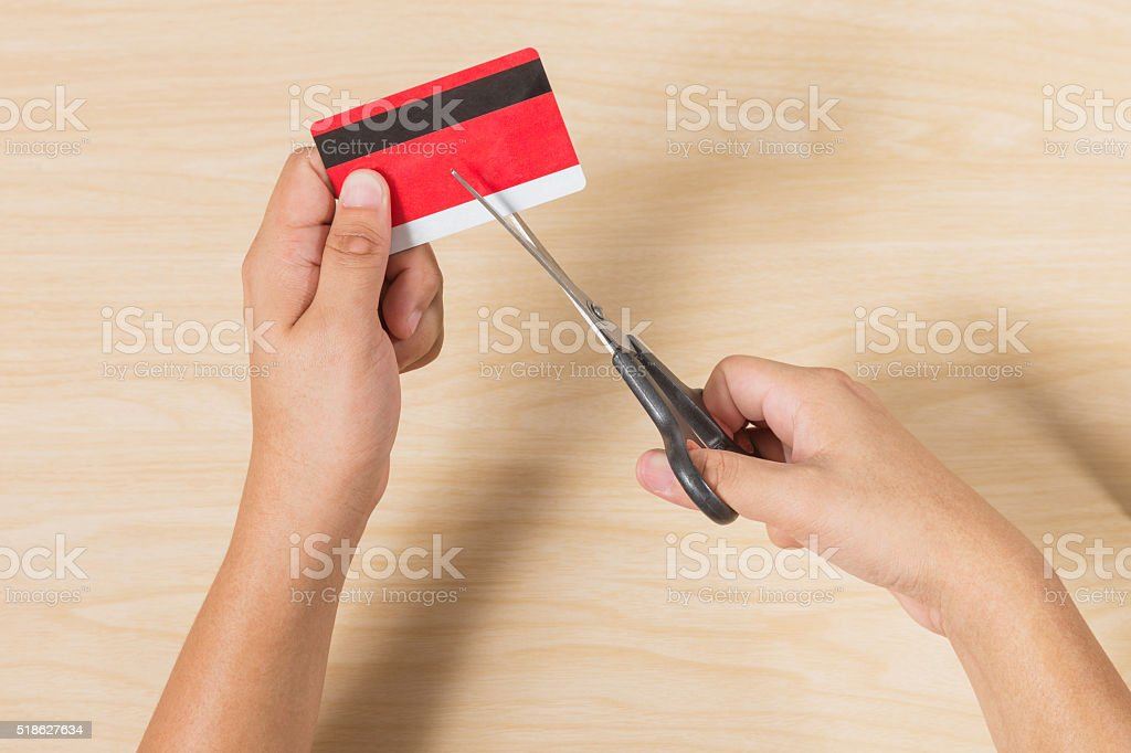 Hands cutting a credit card with scissors stock photo