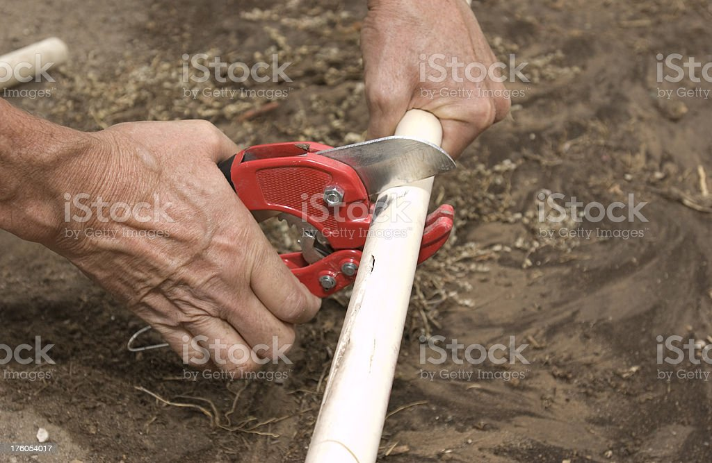 Hands Cutting PVC Irrigation royalty-free stock photo