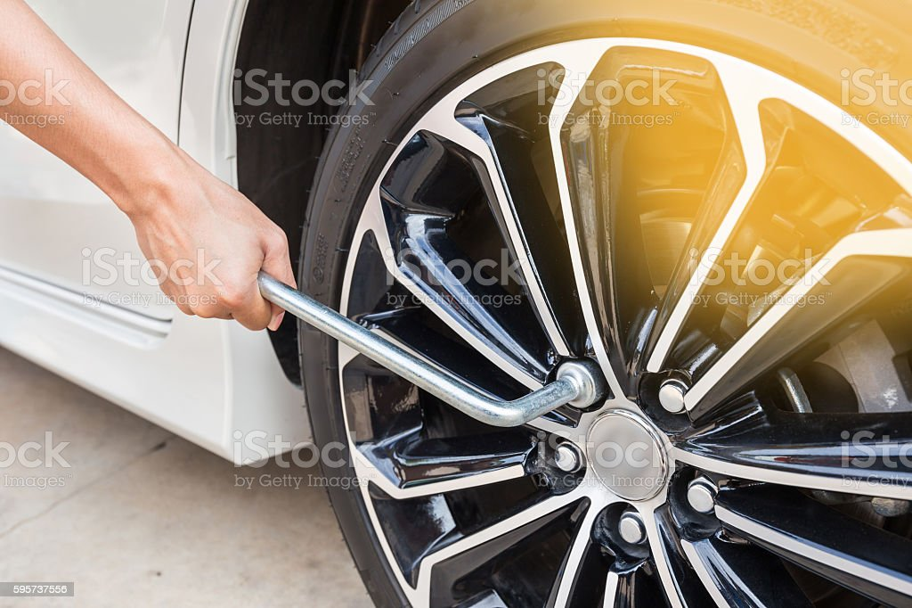 Hands disassembling a modern car wheel (steel rim) stock photo
