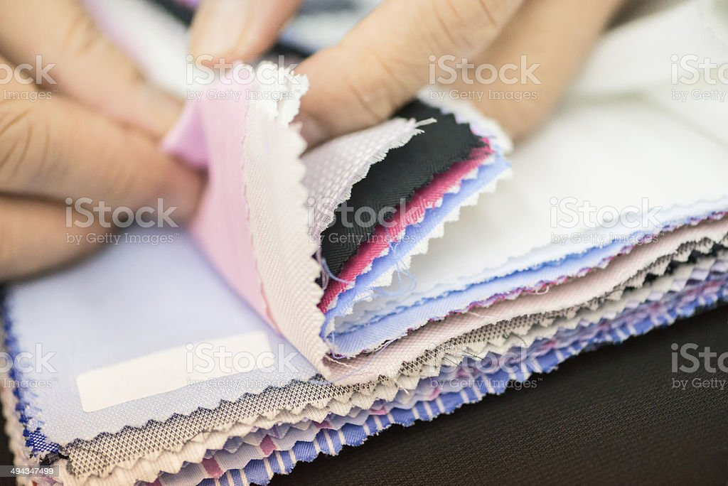 Hands Examining Fabric Samples stock photo