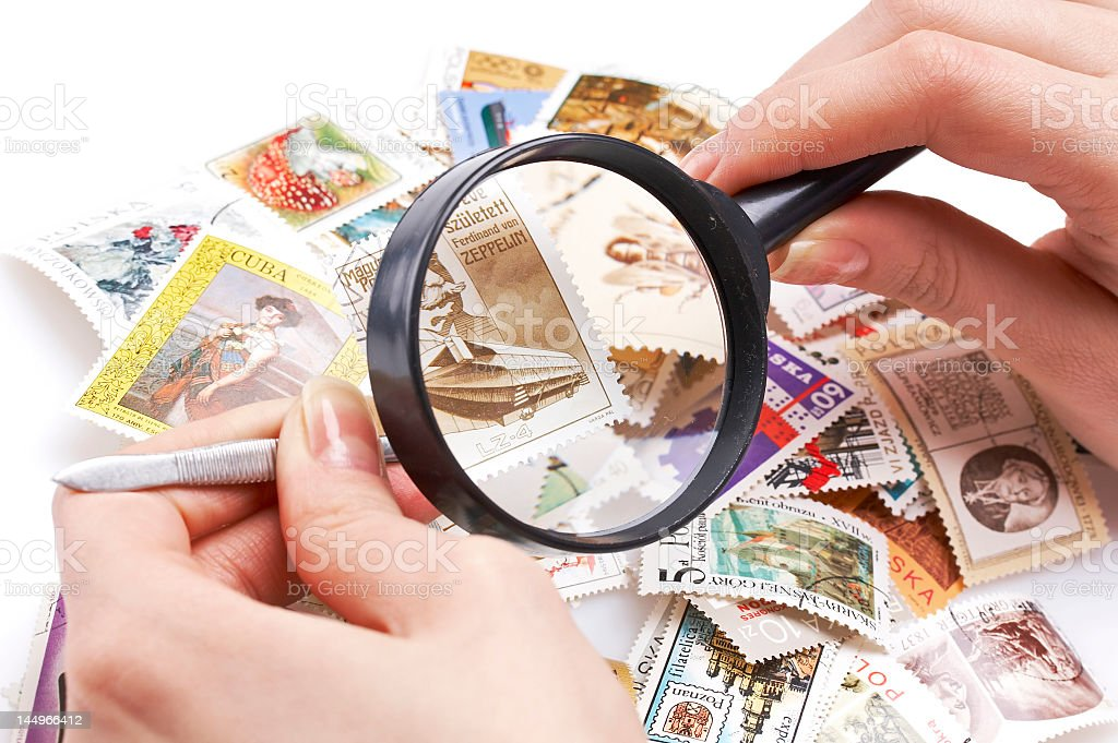 Hands examining stamps under magnifying glass stock photo