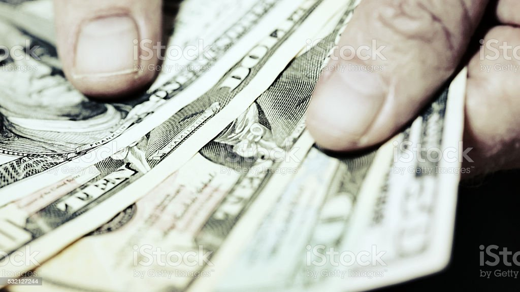 Hands fan out sheaf  of American banknotes stock photo