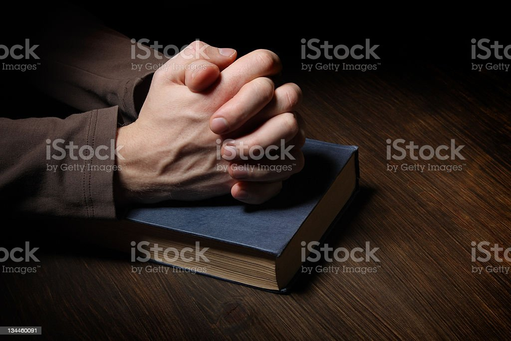 Hands folded in prayer over a Holy Bible stock photo