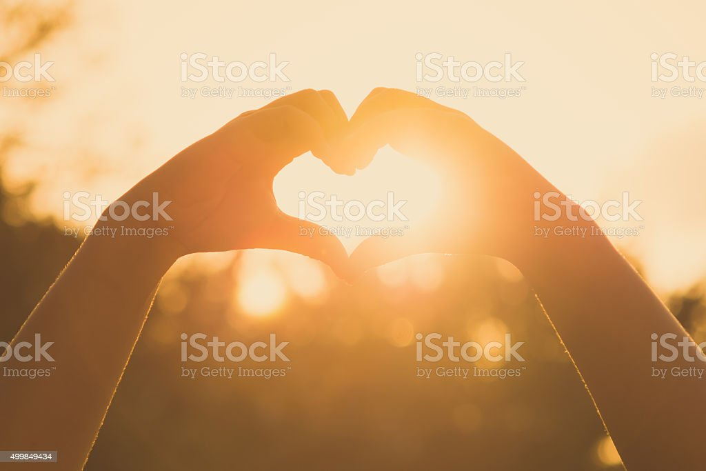 hands forming a heart shape at sunset stock photo