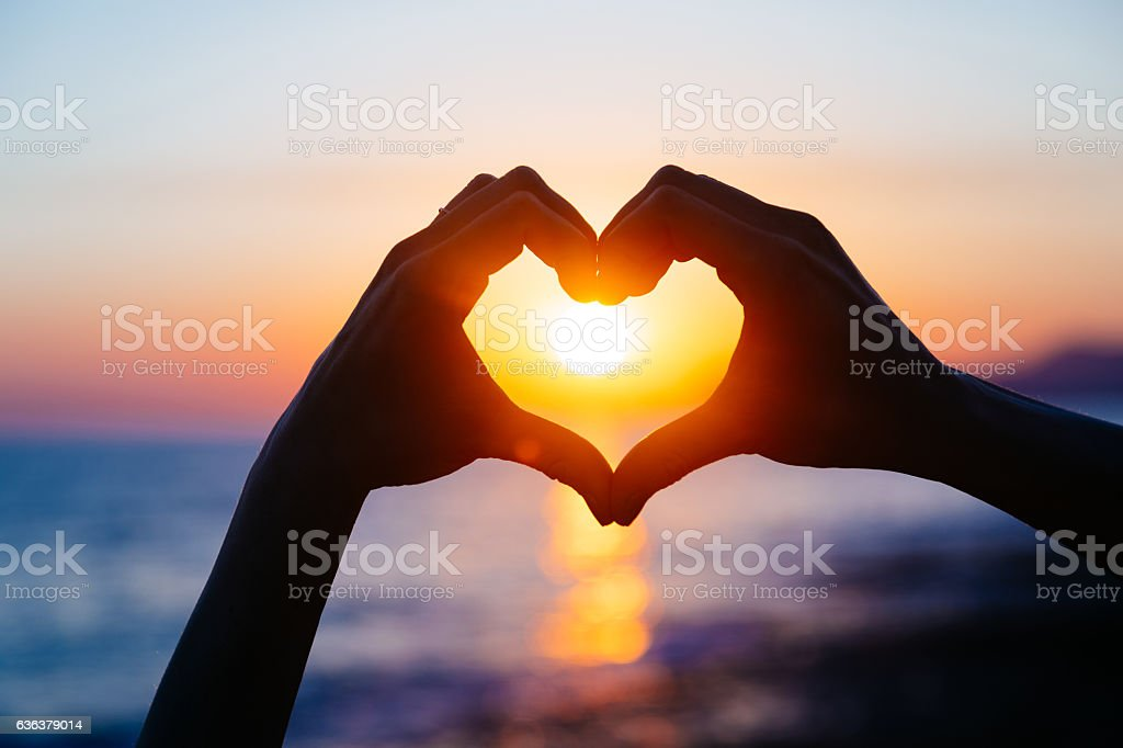 hands forming a heart shape with sunset silhouette stock photo