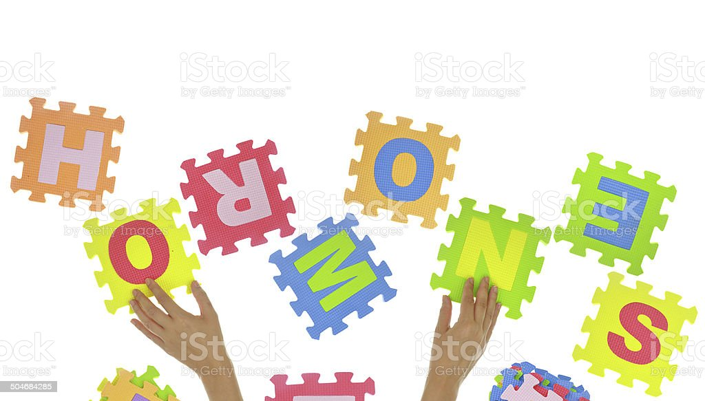 Hands forming word 'Hormones' with jigsaw puzzle pieces isolated stock photo