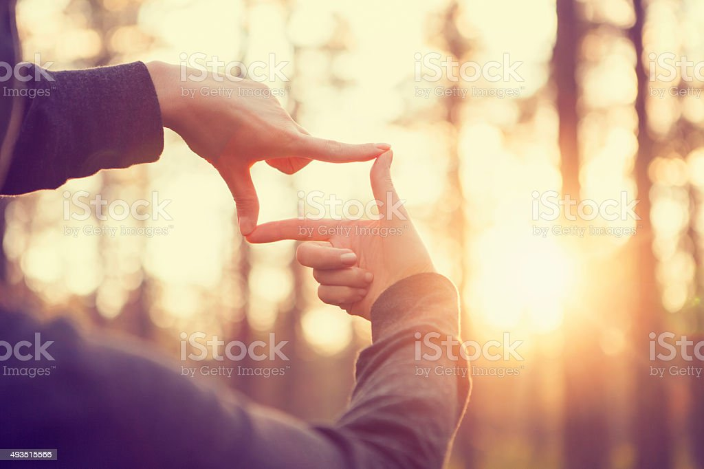 Hands framing distant sun rays stock photo