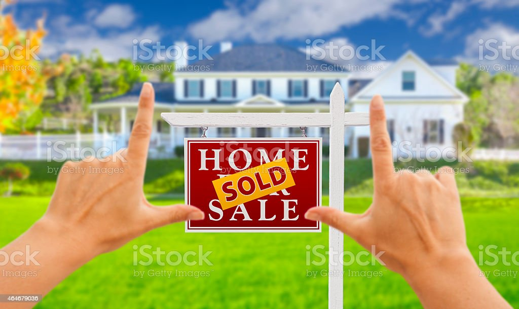 Hands Framing Sold For Sale Real Estate Sign and House stock photo
