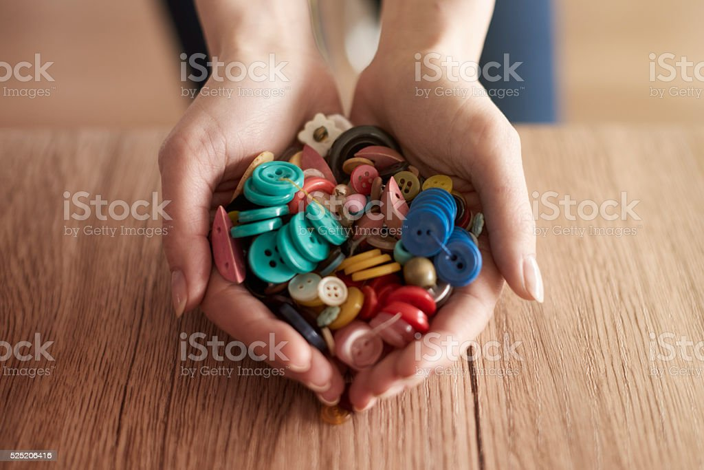 Hands full of colorful buttons stock photo