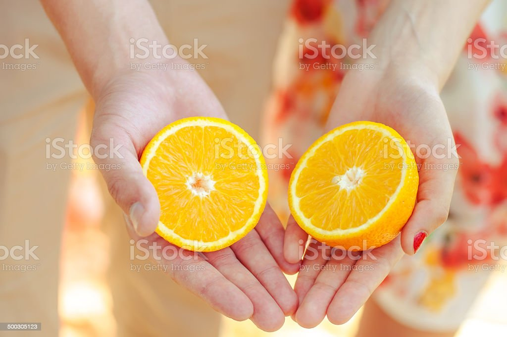 Hands girls and a guy with oranges in summer stock photo