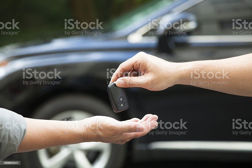 hands giving and receiving car key stock photo