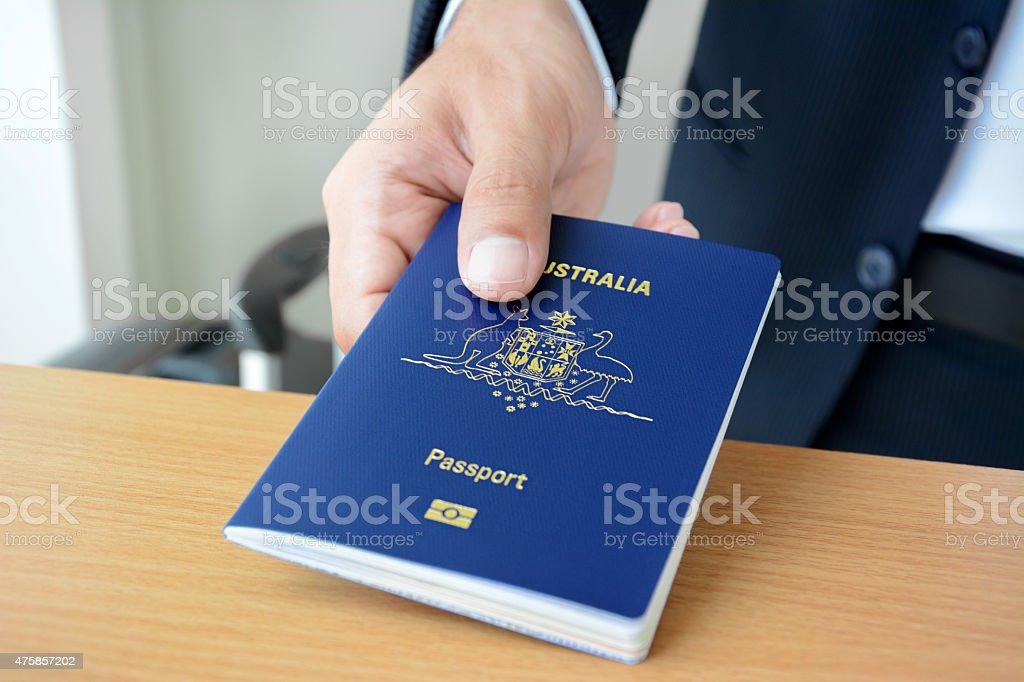 Hands giving passport (of Australia) stock photo
