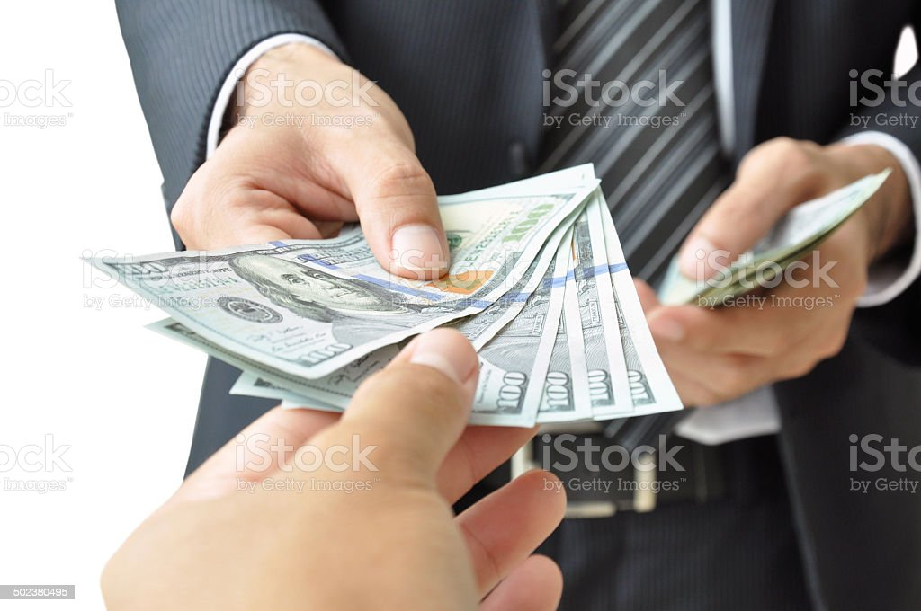 Hands giving & receiving money - United States Dollars (USD) stock photo