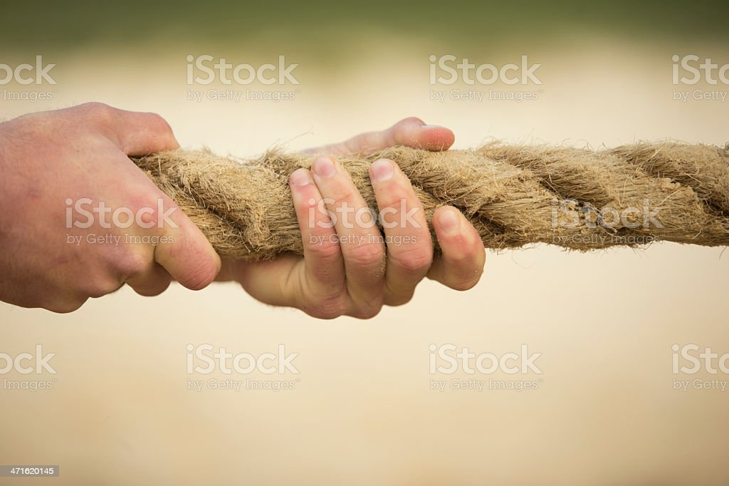 Hands gripping a thick rope tight stock photo