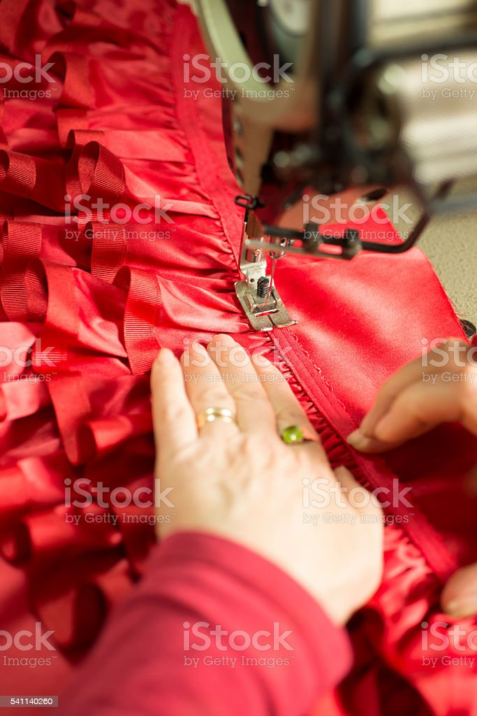 Hands Guiding Red Cloth Through Sewing Machine stock photo