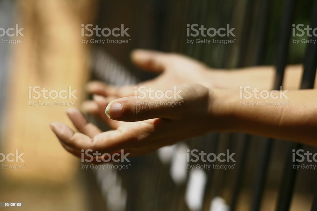 Hands held out from behind bars royalty-free stock photo