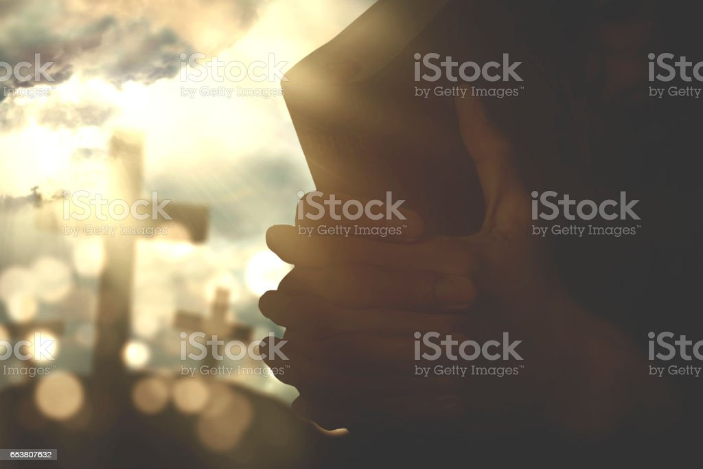 Hands hold a bible and praying stock photo