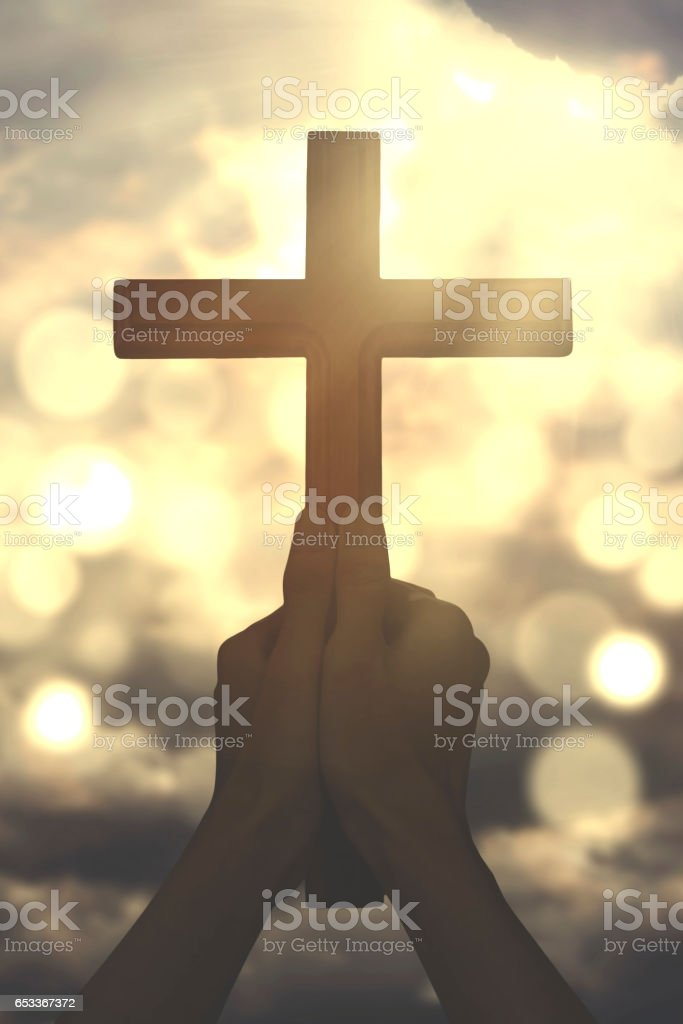 Hands hold a cross with sunbeam stock photo