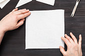 hands hold blank piece of paper on table
