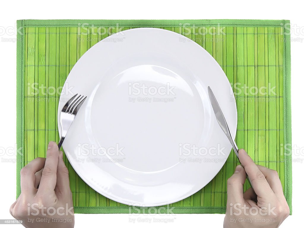 Hands hold fork and knife above plate. royalty-free stock photo