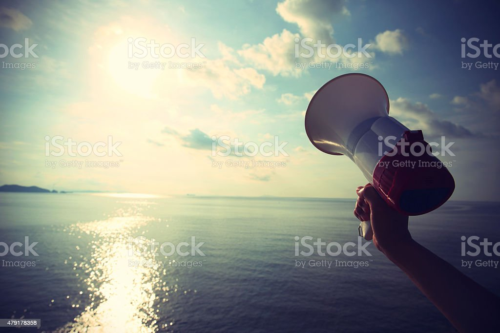 hands hold megaphone with sea under blue sky background stock photo