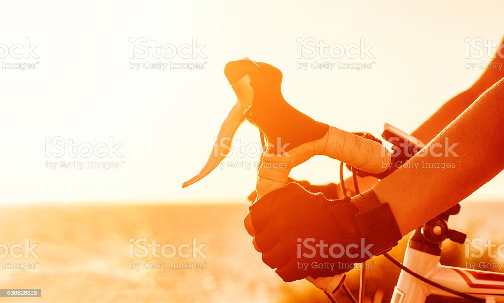 Hands hold on to handlebar on professional racing bicycle stock photo