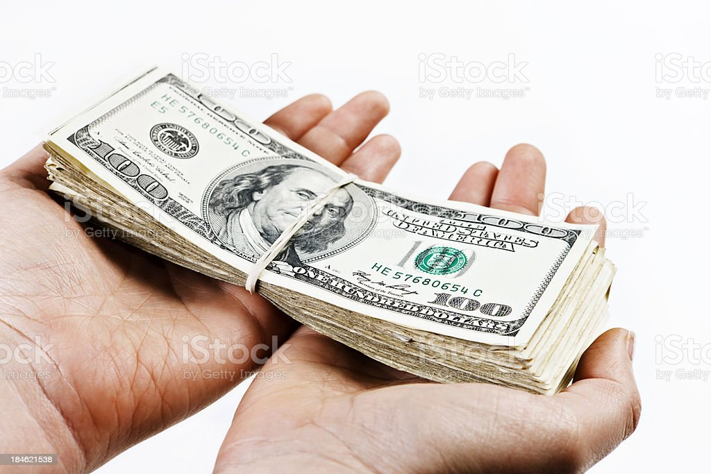 Hands hold out large bundle of US dollars stock photo