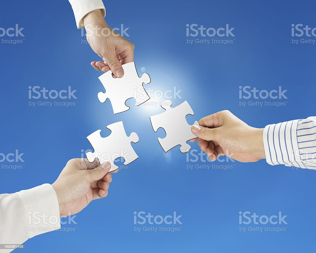 Hands hold puzzles with clear blue sky and sun light stock photo