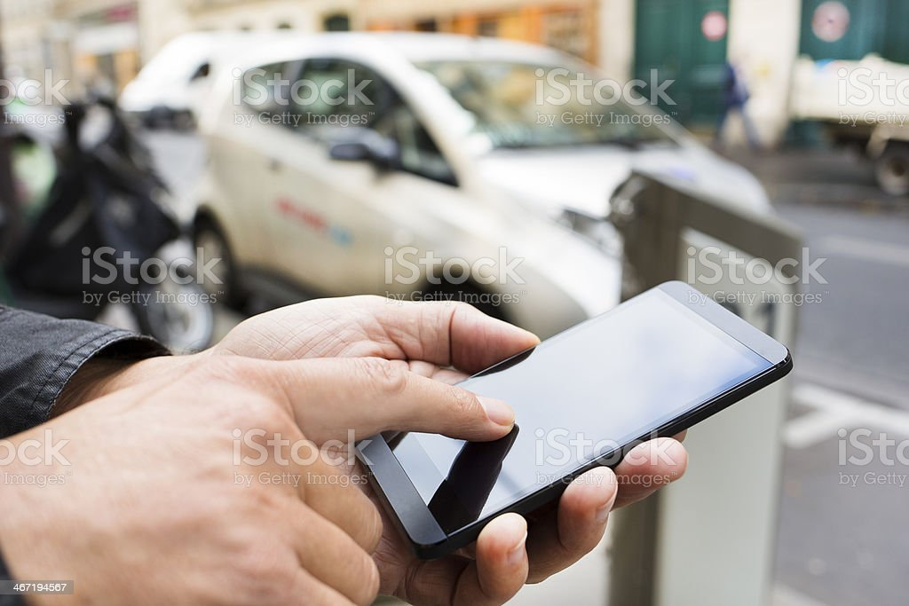 Hands hold smartphone at Autolib Station in Paris stock photo