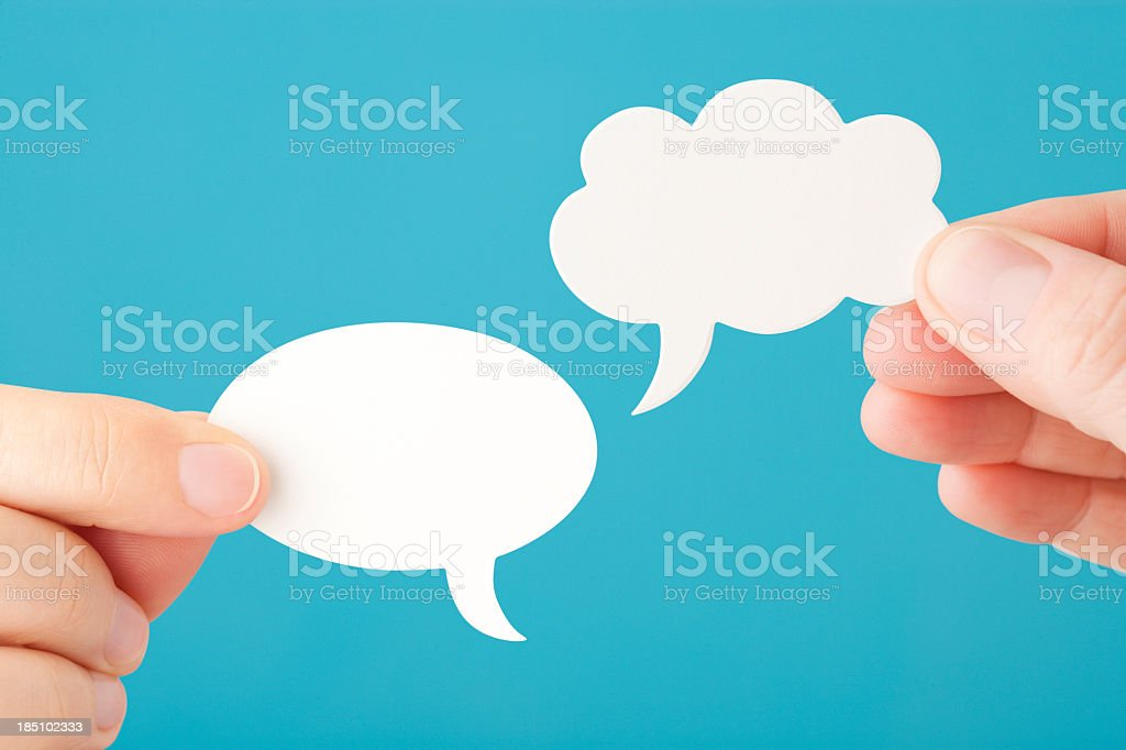 Hands hold two blank speech bubbles stock photo
