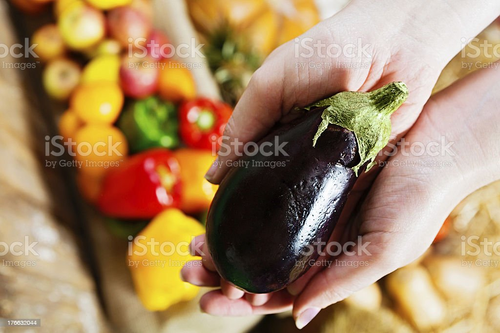 Hands hold up shiny purple aubergine against more vegetables royalty-free stock photo