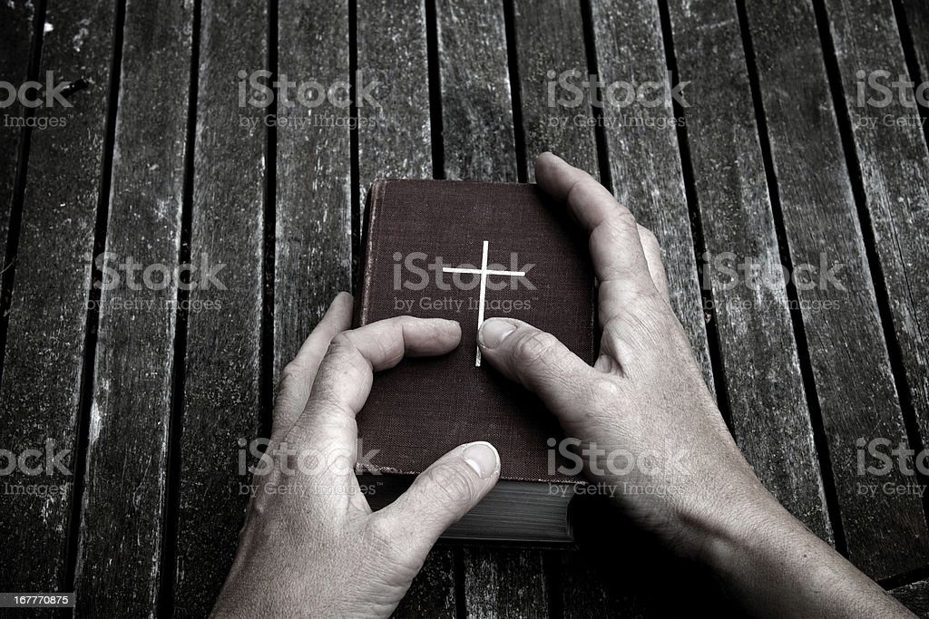 Hands holding a Bible atop a dark wooden surface stock photo