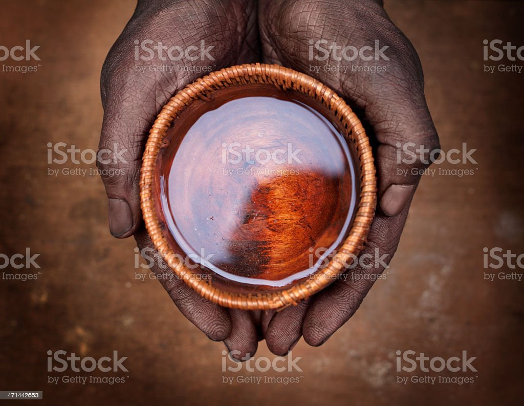 Hands holding a bowl with water stock photo