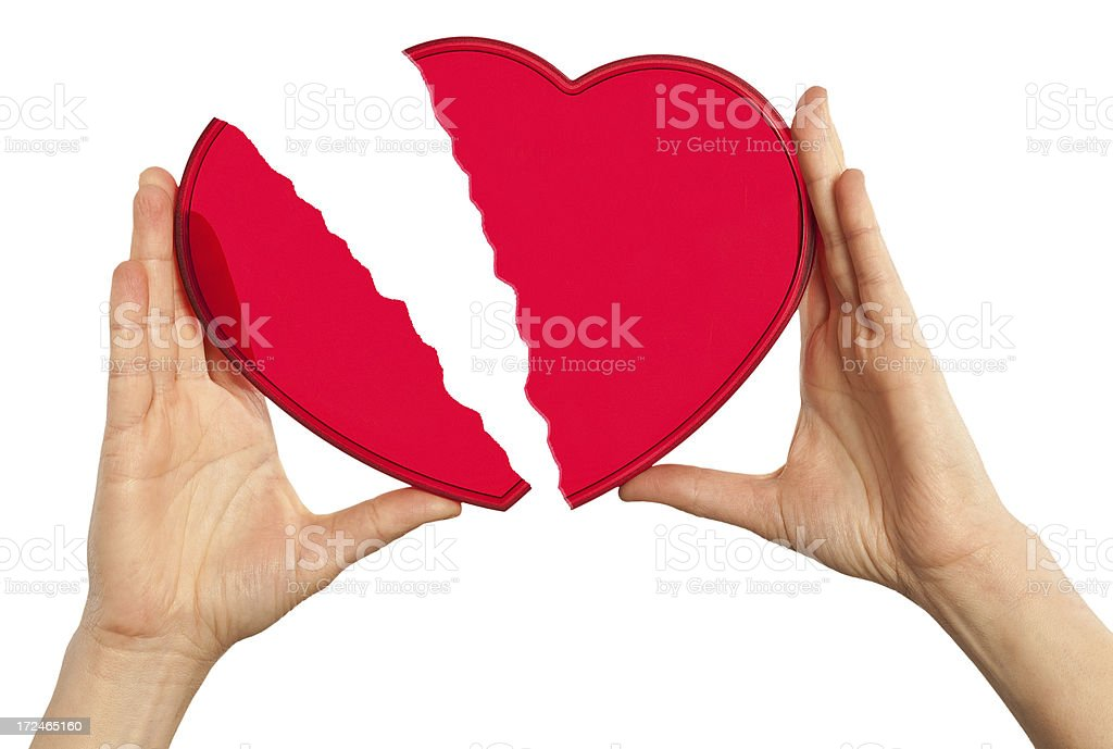 Hands holding a broken red heart isolated on white. royalty-free stock photo