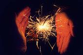 hands holding a burning sparkler