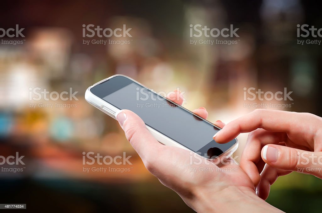 Hands holding a cellphone (smartphone) with tuchscreen in night stock photo