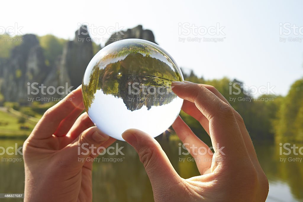 Hands holding a glass sphere in Teutoburg, Germany stock photo