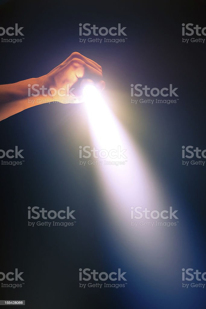 Hands holding a glowing pocket flashlight in the dark stock photo